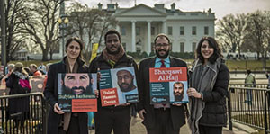 CCR lawyers and legal advocates holding images of GITMo clients